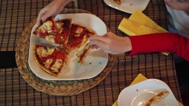 Children taking pizza slices.