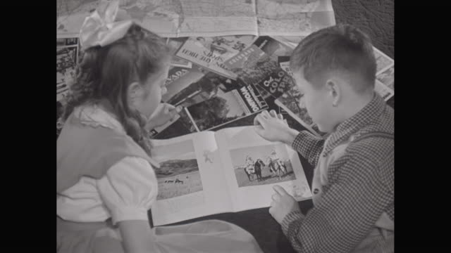 MS HA Children talking and looking at a picture book and travel literature / United States