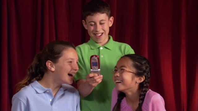 children text messaging on cell phone / los angeles, california - 男性と複数の女性点の映像素材/bロール