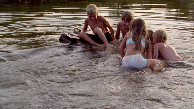 Children trying to climb onto small wooden raft in pond / falling off raft