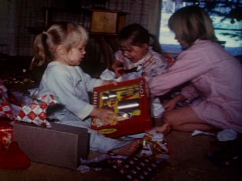 Children unwrap their Christmas presents.