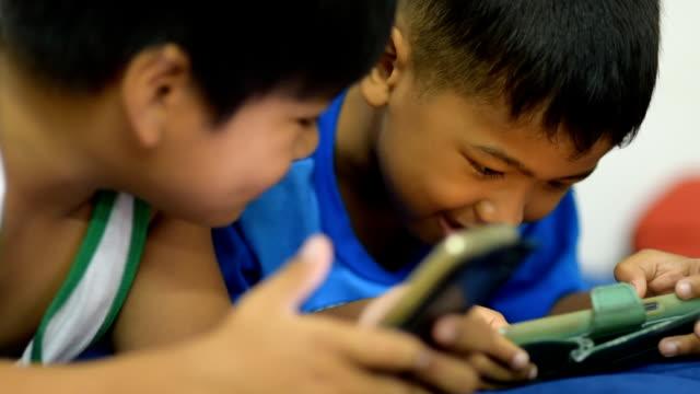 barn använder smart telefon spela spel för underhållning. - människofinger bildbanksvideor och videomaterial från bakom kulisserna