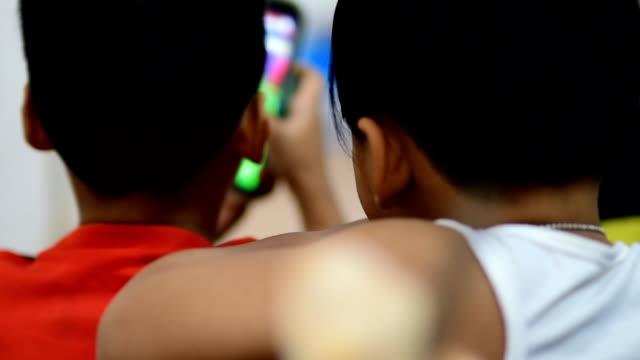 vídeos y material grabado en eventos de stock de los niños usan el juego de teléfono inteligente. - nativo digital