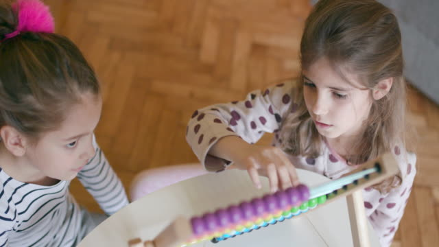 Children using abacus, handheld shot, high angle view