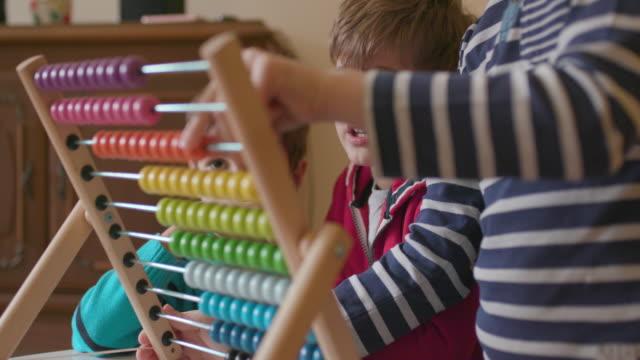 Children using abacus, handheld shot
