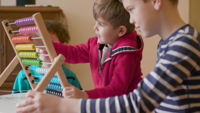 vídeos de stock, filmes e b-roll de crianças usando o ábaco, câmera lenta, tiro portátil - mãos juntas