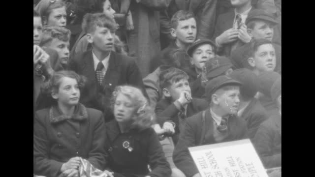 cu children wait for procession one girls chews on sandwich / cu boys in crowd react with cheers as horsedrawn carriage passes / vs crowd of school... - coronation stock videos and b-roll footage