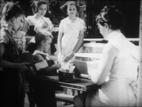 b/w 1934 children waiting in line at librarian's table by bookmobile outdoors / newsreel - librarian stock videos & royalty-free footage