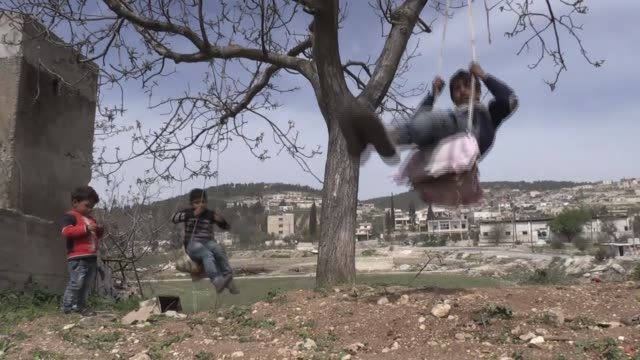 children walk and play around at rural area in afrin town center, as life returns back to normal following the area cleared of ypg/pkk terror groups,... - isil konflikt stock-videos und b-roll-filmmaterial