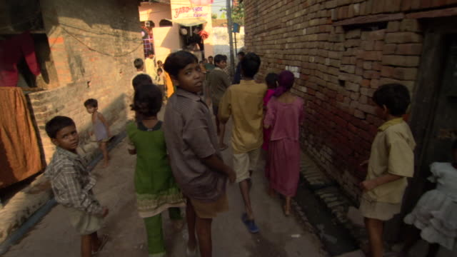 Children walk down alley to village gathering, Agra, Uttar Pradesh, India