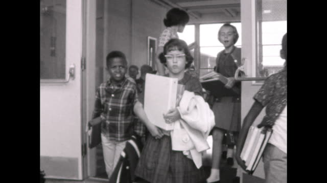 children walk out of school wait outside the school with teachers flag pole with american flag and pennant flag police officer directing traffic - separation stock videos & royalty-free footage