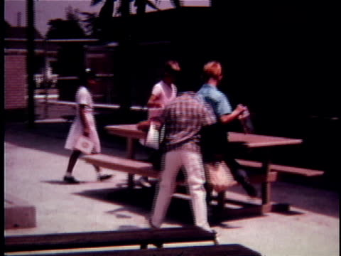 montage ws pan children walking across schoolyard and sitting down at picnic table / ms children opening lunch boxes and taking out food / oakdale, california, usa - papperskasse bildbanksvideor och videomaterial från bakom kulisserna