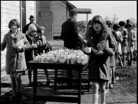children walking in a line outside some buildings / children walking into a building / children each taking a cup from a table they walk past / close... - 1931年点の映像素材/bロール