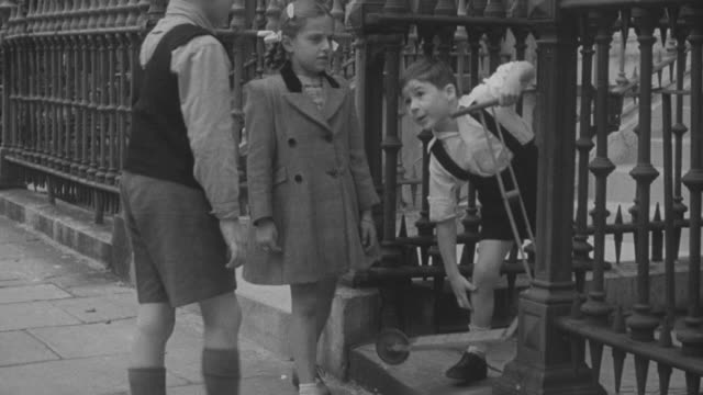 1947 ts children walking on sidewalk and riding a scooter / united kingdom - scooter stock-videos und b-roll-filmmaterial