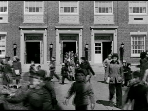 vídeos de stock e filmes b-roll de children walking out of large school and down sidewalk children walking together holding hands some with arm around the other - 1947
