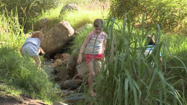 Children walking over rocks in river