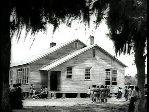 1939 ws children walking toward school building - 分校点の映像素材/bロール
