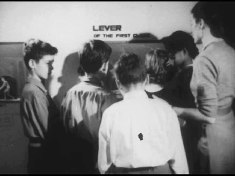 vídeos de stock, filmes e b-roll de / children wandering through museum display; lady guides them / close up interactive display demonstrating how a lever works / shots of young boys on... - 1951