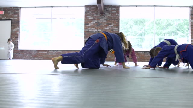 vídeos de stock e filmes b-roll de children warming up for jiu-jitsu class - artes marciais