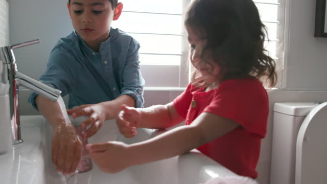 children washing their hands together at home - domestic bathroom stock videos & royalty-free footage