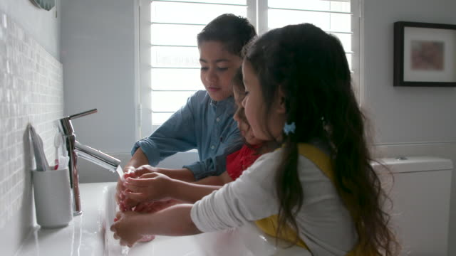 bambini che si lavano le mani insieme - bagno video stock e b–roll