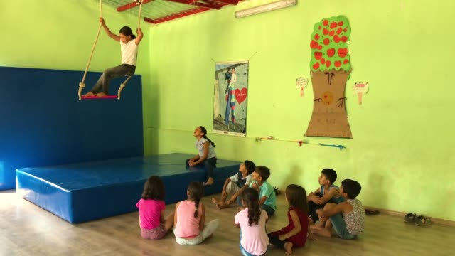 Children watch on as a girl takes part in a trapeze workshop at the Istasyon Sirkhane Center on July 24 2018 in Mardin Turkey The circus school or...