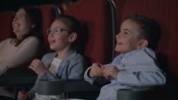Children watching movie enthusiastically in cinema. Child entertainment concept