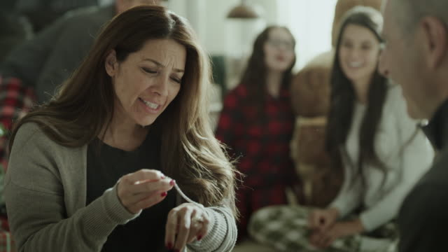 vídeos de stock, filmes e b-roll de children watching smiling mother receiving bracelet from man on christmas / orem, utah, united states - orem