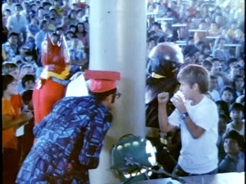 vidéos et rushes de 1975 montage children watching super-hero characters in costumes performing mock battles on stage at children's entertainment show/ hawaii islands, usa hawaii - donner un coup de pied