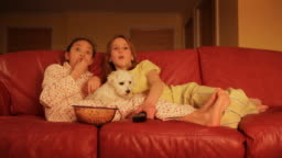 Children watching television with pet  dog