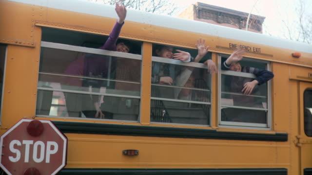 vídeos de stock e filmes b-roll de children waving from school bus - childhood