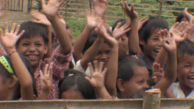 MS Children waving hands / Centro Morangan, Mindoro, Philippines