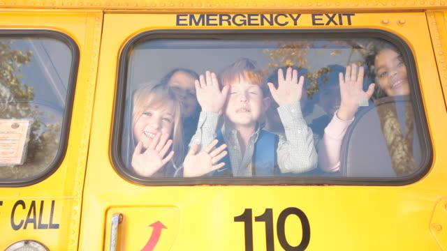 children waving out the back window of a school bus - winken stock-videos und b-roll-filmmaterial
