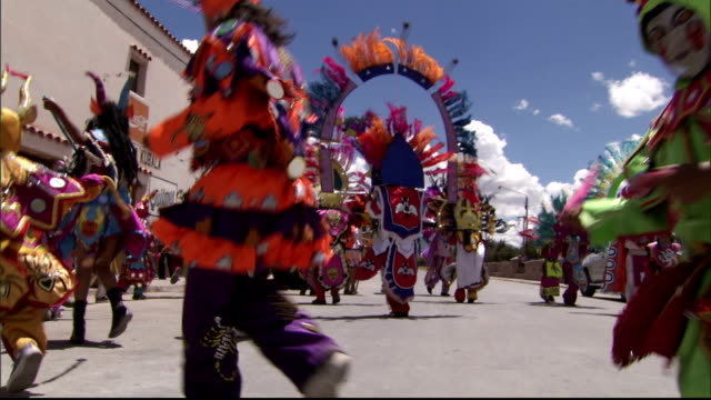 Children wear costumes and headdresses during a parade in the city of Humahuaca. Available in HD.
