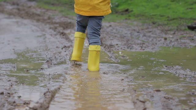 children  wear yellow boot and they are walking on the muddy road - boot stock videos & royalty-free footage
