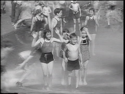 vídeos y material grabado en eventos de stock de b/w 1937 children with bathing suits playing in water from hoses on city street - traje de baño de una pieza