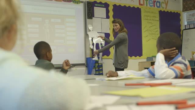 children with female teacher learning  - braccio umano video stock e b–roll