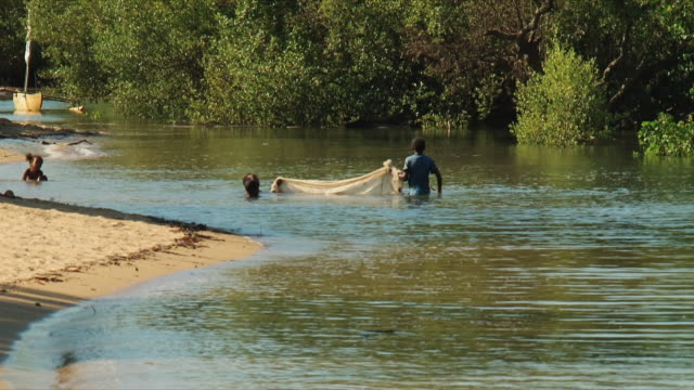 ws children with fishing net wading in see / nosy be, madagascar - waist deep in water stock videos and b-roll footage