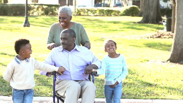 Children with grandparents at park, man in wheelchair