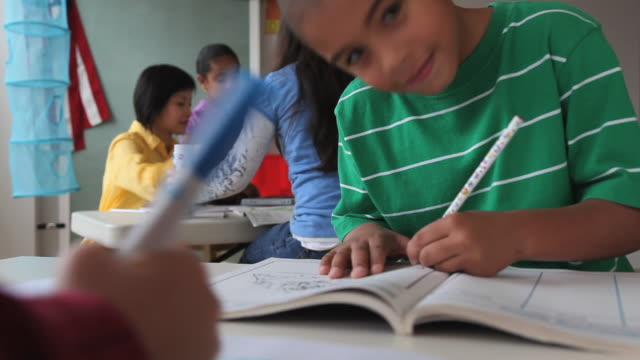MS SELECTIVE FOCUS Children (6-7) writing in classroom / Jersey City, New Jersey State, USA