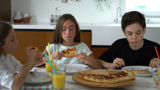 childrens are eating pizza together