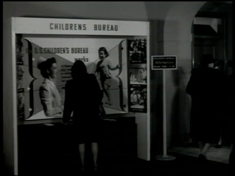 vídeos de stock, filmes e b-roll de children's bureau building. int lobby. int office w/ women working at table putting pamphlets together in mailing envelopes. director of children's... - publicação