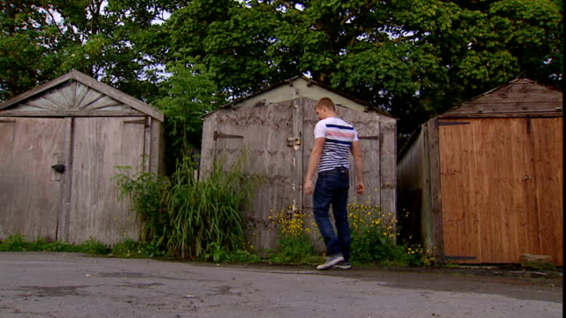 vídeos de stock, filmes e b-roll de children's care system failing young people; england: location unknown: ext various shots of luke rodgers looking at outhouse or shed where he'd... - dependência