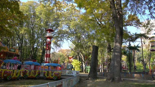 children's carousel at an amusement park with fall foliage trees on a sunny day. beautiful landscape of fall foliage against a bright blue sky in the... - pavel gospodinov stock videos & royalty-free footage