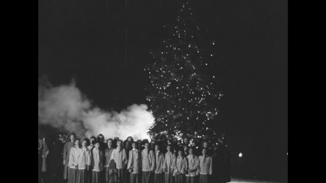 vidéos et rushes de children's choir singing in front of big lighted christmas tree at night smoke billowing out from behind tree / part of tree and smoke pan down to... - choeur