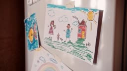 Children's colorful drawings on refrigerator door in family house kitchen
