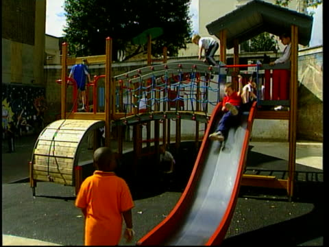 childrens petition for safe play areas itn england london children playing in playground lms children playing in playground as young boy slides down... - health and safety点の映像素材/bロール