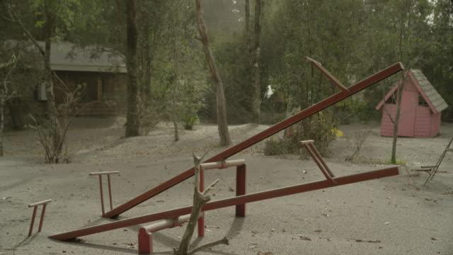 ensenada, chile - april 27, 2015: children's playground covered in volcanic ash - altalena video stock e b–roll