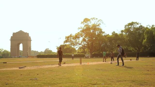 ws childrens playing cricket in garden near india gate monument / delhi, india   - cricket stock-videos und b-roll-filmmaterial