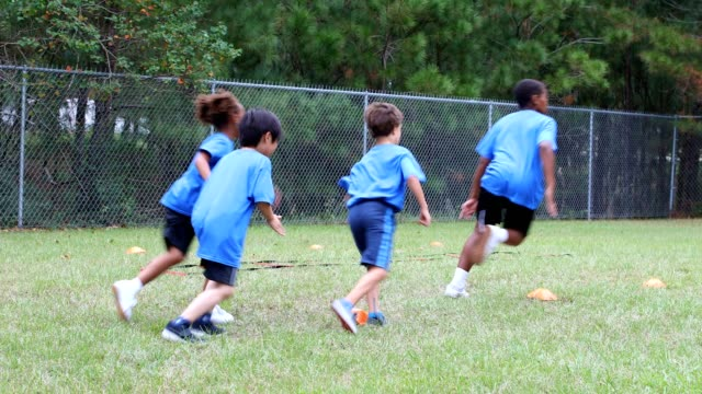 Children's soccer team players run around cones in a field performing a drill.